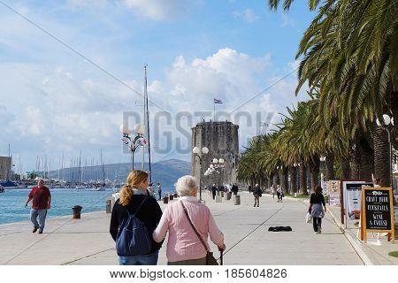 TROGIR, CROATIA - OCTOBER 20, 2016: Tourists walks on sea promenade of old town that is UNESCO heritage