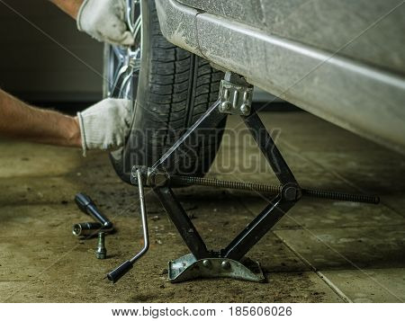 Male hands screwing in the wheel of the car. Replacement rear wheel vehicle mechanic in the garage.
