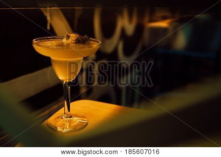 Yellow cocktail with apple in a cocktail glass