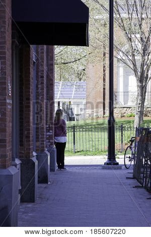 Burlington, Vermont - May 1, 2014 - Vertical from the back of a girl waiting for a bus at the end the