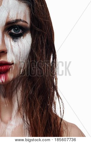 Beauty Brunette with Ethnic Face Art. Wet Hair and smeared white Paint on Skin