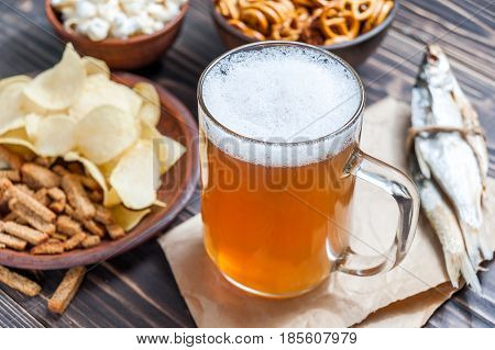 Lager Beer Mug And Snacks On Wooden Table. Nuts, Chips, Crackers And Dry Fish