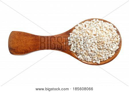 Barley groats on wooden spoon isolated on white background . Top view.