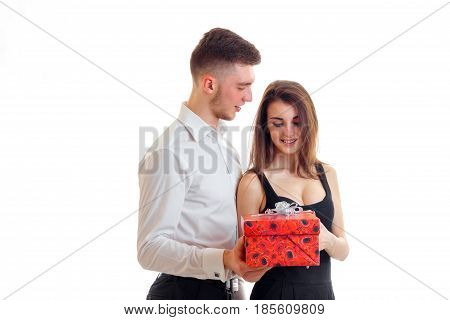 a young guy in a white shirt brought the girl to a big red gift isolated on white background