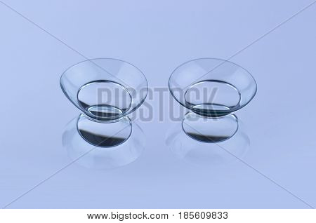 Contact lenses on blue background with reflection.
