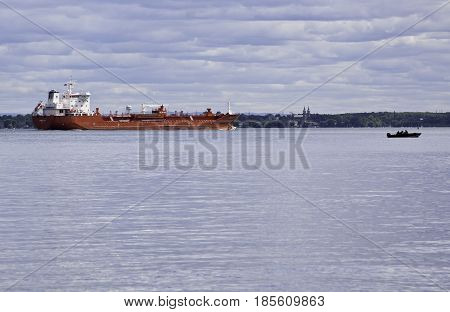 Notre Dame de Ile Perrot, Quebec - June 20, 2014 -- Wide landscape view of a very large red cargo ship and a very small boat motor boat in Lake St-Louis in Notre Dame de Ile Perrot, Quebec with trees foliage in the background on a sunny day in June.