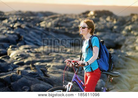 Young Tourist Cycling On Lava Field On Hawaii. Female Hiker Heading To Lava Viewing Area At Kalapana