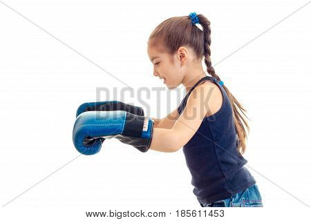 little girl with pigtail stands sideways and extended her hand in big boxing gloves is isolated on a white background