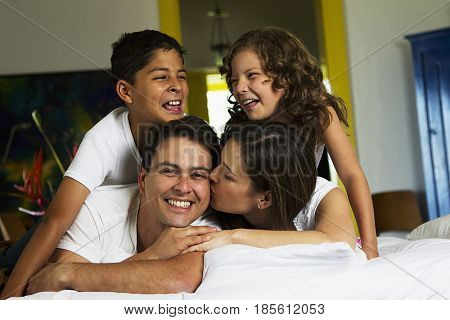 Smiling Hispanic family laying on bed together