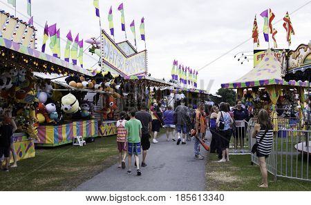 Cornwall, Quebec - July 26, 2014 - Wide view of the crowd of people checking out the colorful carnival section of the Ribfest in Cornwall, Ontario on a sunny afternoon in July.
