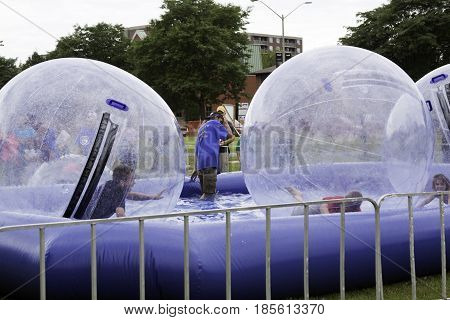 Cornwall, Quebec - July 26, 2014 - Wide view of children playing inside large plastic bubbles in a pool at the Ribfest in Cornwall, Ontario on a sunny afternoon in July.
