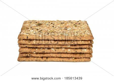 a pile of some appetizing brown crackers topped with different seeds on a white background