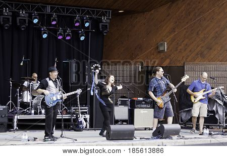 Cornwall, Quebec - July 26, 2014 -- Wide view of a band playing pop music at the Ribfest in Cornwall, Ontario on a sunny afternoon in July.