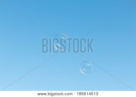 Isolated soap bubbles against a bright blue sky