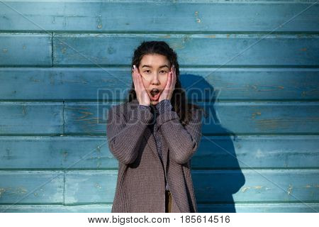 Asian Girl Opens Her Mouth In Surprise And Clasps Her Face In Her Palms