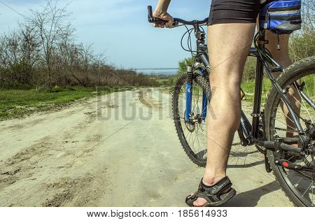 A young guy on a bicycle became near the descent of a clay rural road