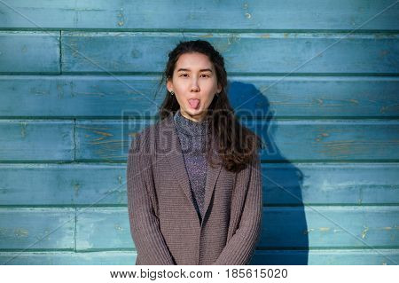 A Beautiful Asian Girl Fools Around And Shows Her Tongue. She Stands By The Wooden Blue Wall. She We