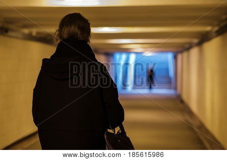 A Girl In Black Clothes Is Walking Along An Underground Passage.