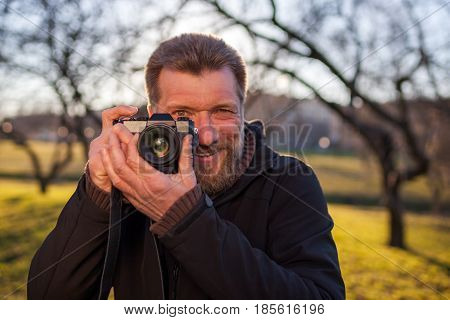 A Mature Man  Takes Pictures On A Mirrorless Camera In The Street. Hobby Of Photography. New Trends