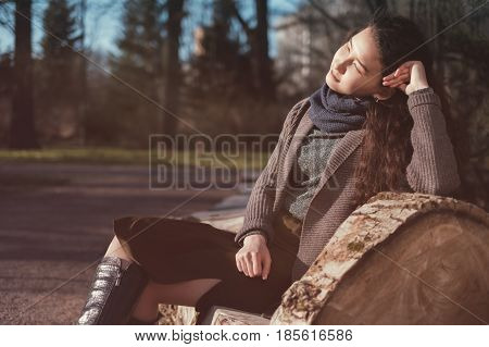 A Beautiful Asian Girl Sits On A Bench And Basks In The Sun In Early Spring Or Autumn