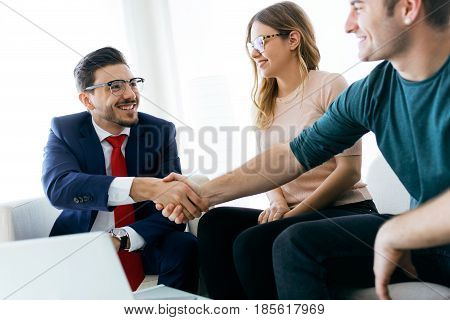 Young Couple In Bank Office Shaking Hand To Financial Adviser.