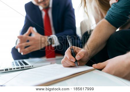 Beautiful Young Couple Signing Financial Contract In The Office.