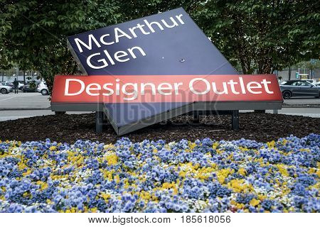 Roermond, Netherlands 07.05.2017 - Entrance sign logo betweeen fowers of the Mc Arthur Glen Designer Outlet shopping area