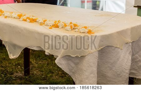 Homemade strudel dough on a traditional linen tablecloth ready for making cottage cheese pie and other pastry. Ingredients of the filling - cottage cheese, nuts, peaches. The process of making pie dough according to the traditional Hungarian recipe.