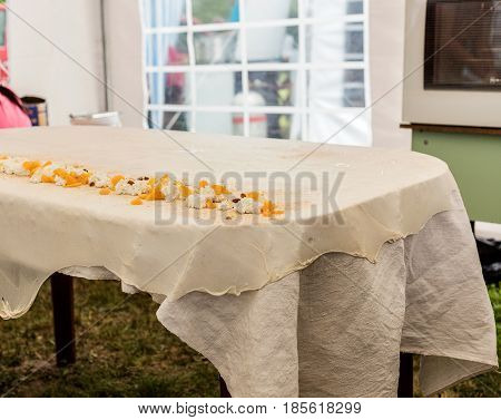 Homemade strudel dough on a traditional linen tablecloth ready for making cottage cheese pie and other pastry. Ingredients of the filling - cottage cheese, nuts, peaches, raisins. The process of making pie dough according to the traditional Hungarian reci