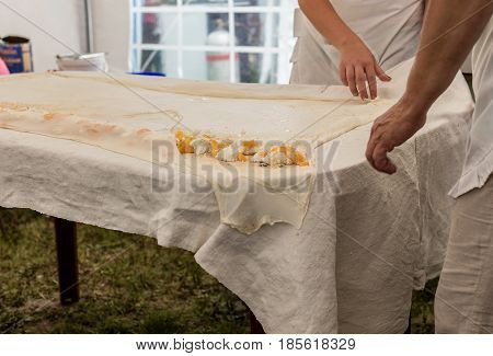 Homemade strudel dough on a traditional linen tablecloth ready for making cottage cheese pie and other pastry. Women roll up the dough with tablecloth. The process of making pie dough according to the traditional Hungarian recipe.