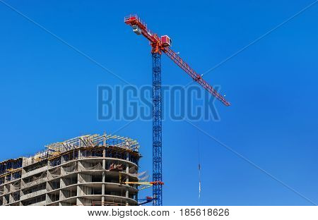 Construction site. Construction crane and high-rise building under construction against blue sky