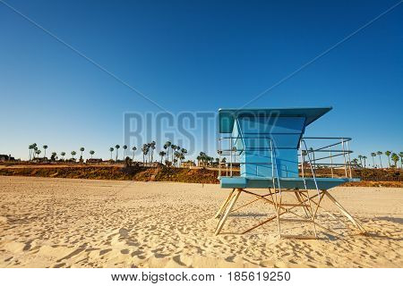 Closed blue lifeguard tower standing on deserted sandy beach of Santa Monica, United States