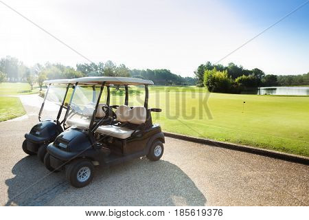 Two electric golf-carts standing at the parking lot of golf club at sunny day
