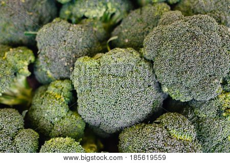 Fresh organic broccoli stand out among many large background broccoli in the market.