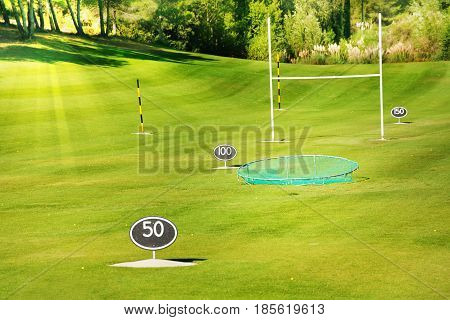 Driving range at golf course with yard signs, flagsticks and balls for practicing swing