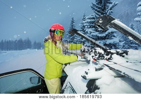 Young woman fastening skis on the roof of car after ski trip during snowfall