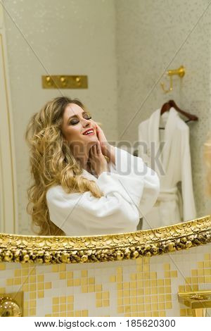 Beautiful blonde girl corrects her hair and looking in the mirror in her bathroom. Beauty young woman orrects her hair. Hairstyling.