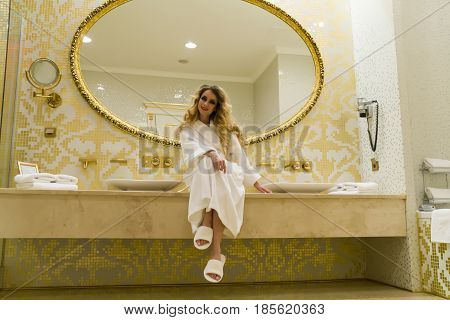 Beautiful seductive woman flirting with the camera is sitting in her bathroom. Beauty young woman.