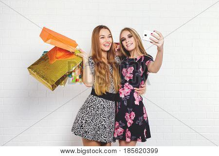 Beautiful teen girls carrying shopping bags and taking selfie over white background