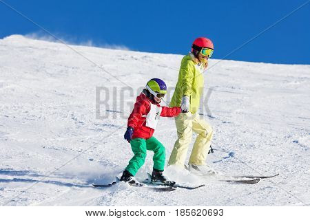 Active mother teaching her son skiing holding hands at snowy mountains