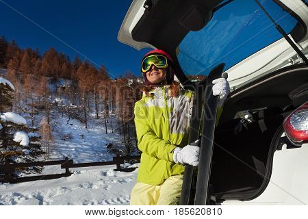 Happy young woman sitting in opened car trunk and holding skis at her hands