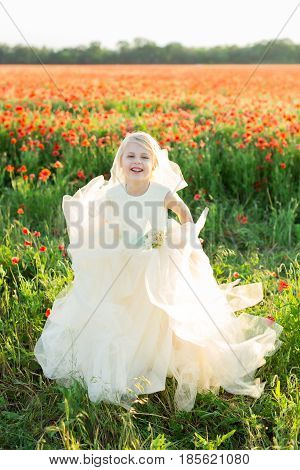 excited child, weekends, celebration, summer, kid fashion concept - little joyful blonde girl in sunday white dress with tulle skirt lughing and jumping in the middle of poppy field