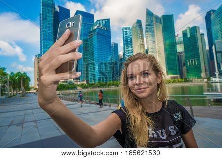 Girl holding smartphone for self-portrait photo with view of modern skyscrapers during summer travel vacation