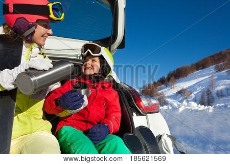 Cheerful mother pouring warm tea from thermos bottle for her son sitting in opened car trunk after skiing
