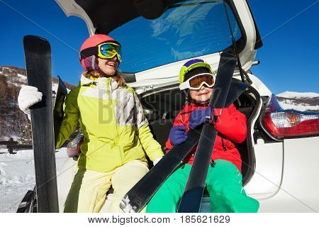 Smiling young woman with her son in skiing suits, sitting in the trunk of a car and holding their skis