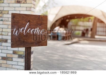 Wedding decor. Wooden plaque with the inscription in paint Welcome. Wood hand made signboard, welcome wedding decoration.