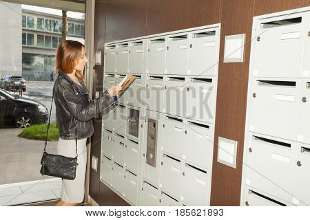 Portrait of young pretty woman taking mail out the mailbox standing at the hall