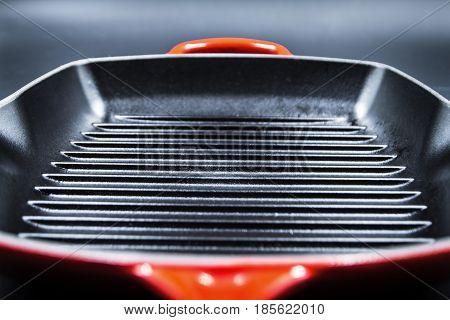 Red cast iron griddle pan on black background