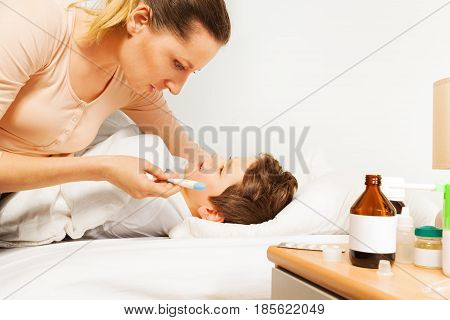 Mother sitting with her sick kid boy on the bed and checking his temperature by electronic thermometer