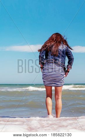 A young woman in a striped dress and a jeans jacket enters the sea. A girl in a jeans jacket dips her feet in the sea. Girl with long hair and sea from the back. A girl with slender legs in the sea.